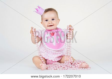 Girl with a crown, sitting in a bib on a white background