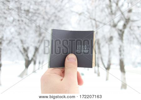 creative concept, man holding a retro book with text hello december