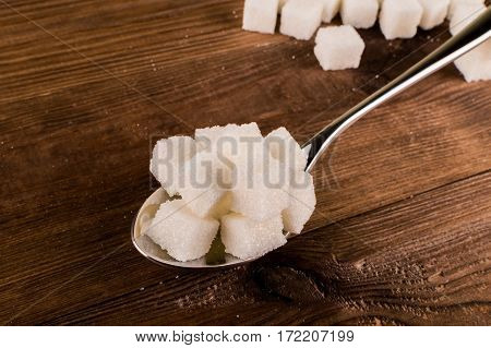 Diabetes. A lot of sugar cubes in spoon.