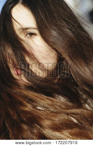 Dramatic fine art portrait of a girl theme. Beautiful lonely girl with flying hair in the wind. Authentic artistic photography.