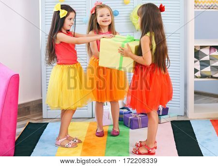 Birthday celebrating. Girls with gift box in room