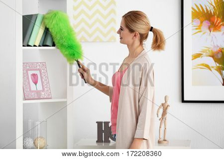 Pretty adult woman cleaning house from dust