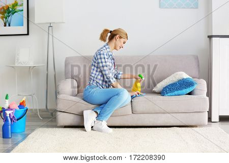 Pretty adult woman cleaning sofa at home