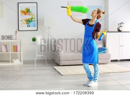 Funny adult woman with duster and detergent in living room