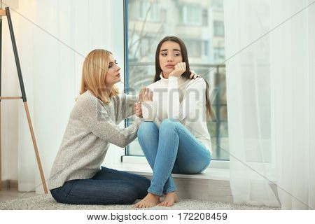 Beautiful woman countenancing depressed friend sitting on window sill at home