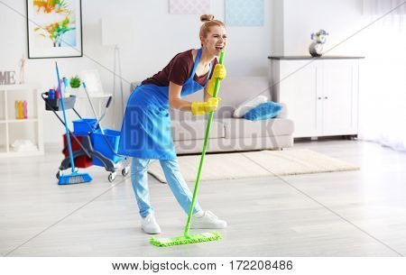 Funny adult woman with mop in living room