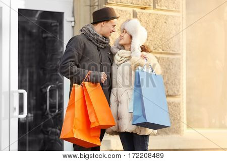 Young couple with colourful shopping bags on the street