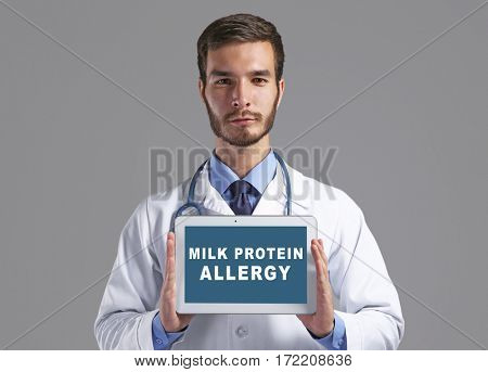 Health care concept. Doctor holding tablet with text MILK PROTEIN ALLERGY on screen against gray background