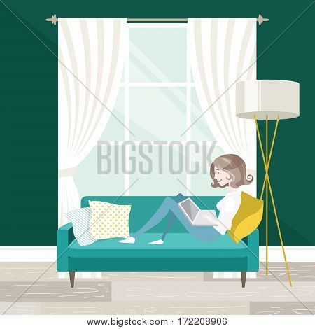 Female freelancer working on her laptop sitting on the sofa