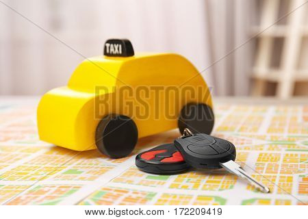 Yellow toy taxi with car key on map