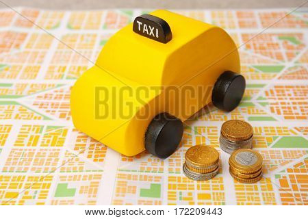 Yellow toy taxi with coins on map background