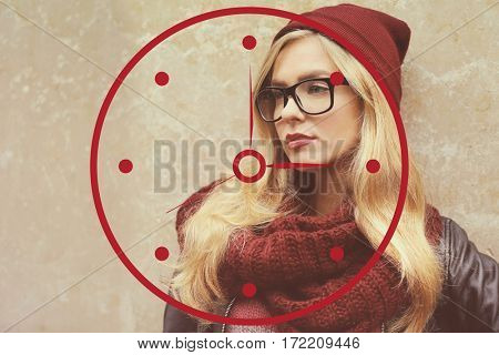 Time concept. Stylish young woman in glasses on wall background