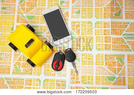 Yellow toy taxi, car key and phone on map