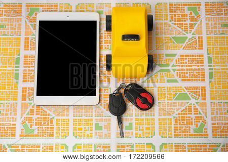 Yellow toy taxi with tablet and car key on map background
