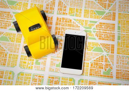 Yellow toy taxi with phone on map background