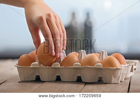 Woman hand taking raw egg from package, closeup