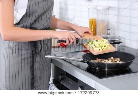 Woman cooking delicious dinner at home