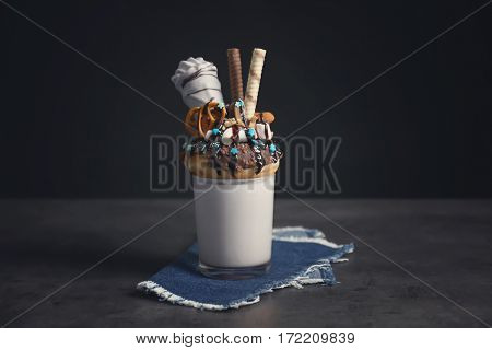 Milkshake, donut and other sweets in glass on dark background