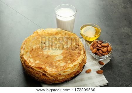 Delicious pancakes, almonds, honey and glass of milk on table