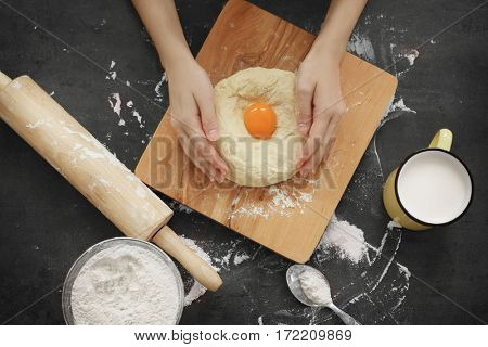 Female hands kneading dough with egg on wooden cutting board, top view