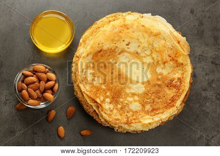 Delicious pancakes, almonds and honey on table