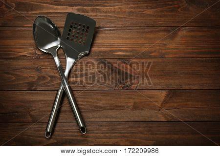 Metal kitchen utensils on wooden table