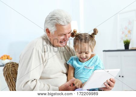Grandfather with his granddaughter using tablet at home