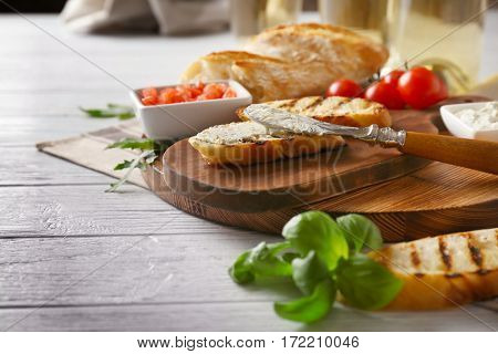 Tasty bruschetta with creamy cheese on wooden board