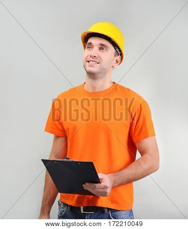 Handsome warehouse worker with clipboard on light background