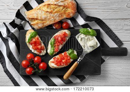 Tasty bruschetta with creamy cheese on wooden board