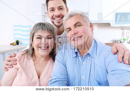 Young man with middle aged parents taking selfie