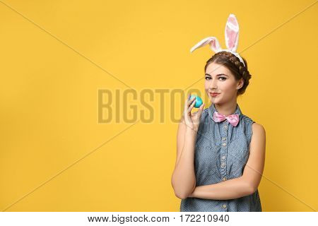 Beautiful young woman with bunny ears and Easter egg on color background