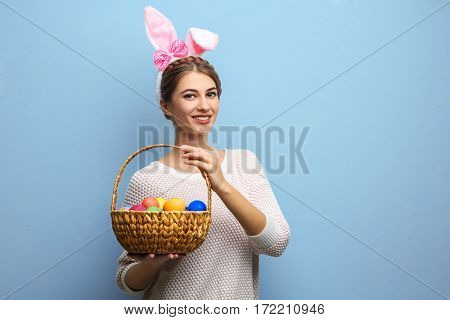 Beautiful young woman with bunny ears and basket full of Easter eggs on light background