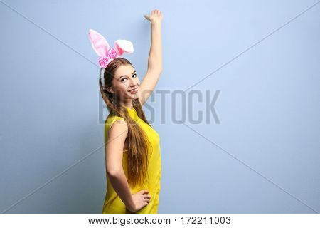 Beautiful young woman with bunny ears on light background