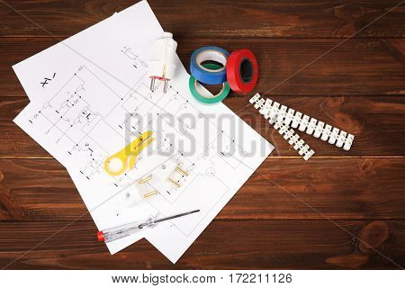 Electrician tools and schemes on wooden background