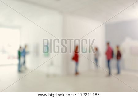 Blurred view of people in modern art gallery hall