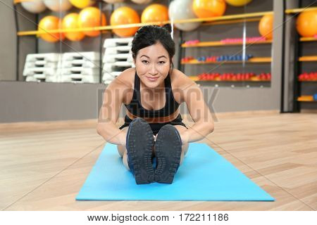 Sporty woman stretching in gym