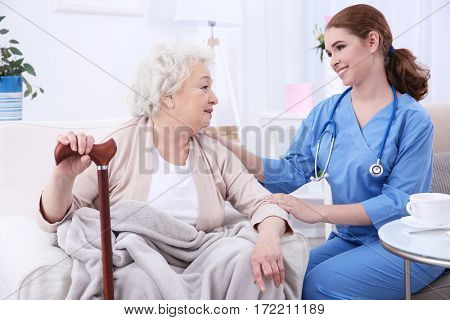 Nurse talking with elderly woman in light room