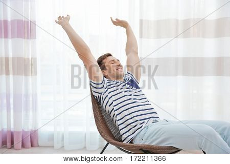 Young man resting on modern chair and stretching himself in light room