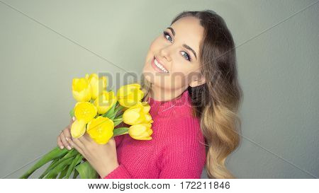 Young beautiful woman holding a bouquet of yellow tulips. Happy girl. Spring.