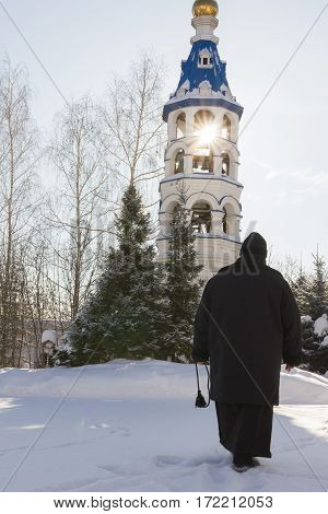Kazan, Russia, 9 february 2017, golden domes in Zilant monastery - oldest orthodox building - a nun holds a rosary in his hands near bell tower, vertical