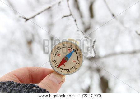 Hand with compass. Traveler searching direction with a compass. On background of winter forest