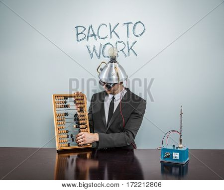 Back to work text on blackboard with businessman and abacus