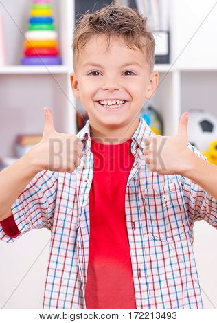 Half-length emotional portrait of caucasian boy making thumbs up gesture. Handsome child laughing looking very happy.