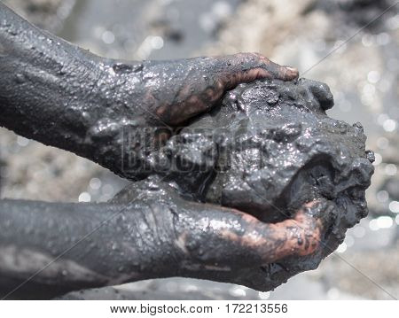 Handful of black healing mud. Hands and arms smeared with this mud. Close-up.