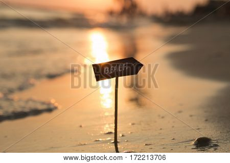 Beach inscription on the sign and beautiful sunset
