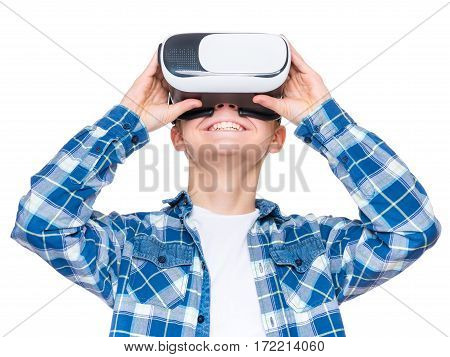 Happy teen boy wearing virtual reality goggles watching movies or playing video games, isolated on white background. Cheerful smiling teenager looking in VR glasses. Funny child experiencing virtual reality. 3D gadget technology.