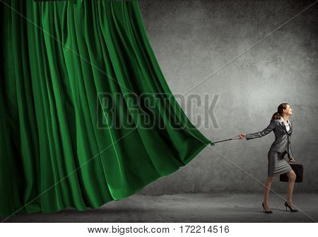 Young businesswoman pulling curtain with lead. Place for text