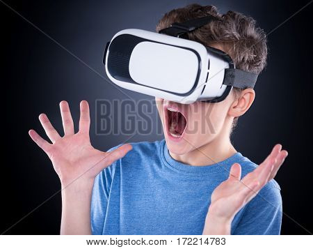 Amazed teen boy screaming, wearing virtual reality goggles watching movies or playing video games. Surprised teenager looking in VR glasses and shouting out loud. Child experiencing 3D gadget technology.
