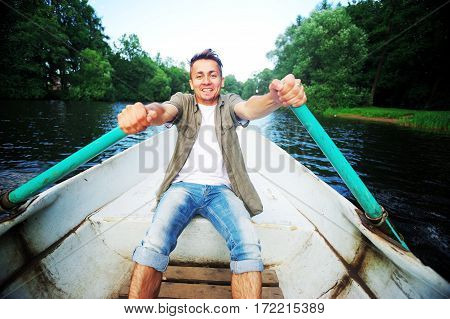 young handsome man swims on a wooden boat and rowing with oars